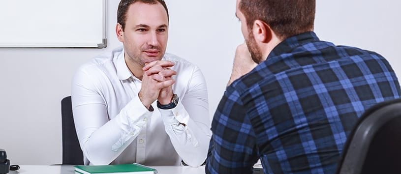 """alt=""""A man in a white collared shirt, presumably an admissions rep, sits across from another man with a trimmed beard, giving him his full attention"""""""