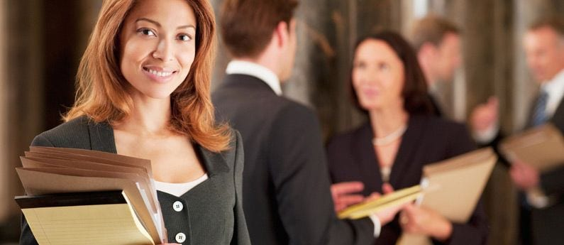An attractive business woman with an equally attractive smile, holding a yellow legal pad and a few folders is looking at you while two pairs of business people chat in the background