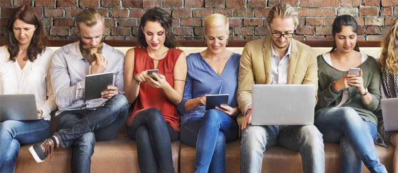 Six mainly caucasian people, two men and four women, all quite fashionably dressed, are sitting on a long couch and every one of them is looking at a screen—laptops, tablets, and phones.